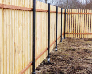 Применение металлических элементов для столбов деревянного забора