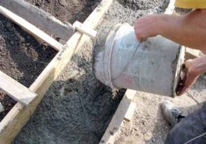 Процесс заливки бетоном ленточной конструкции основания ограждения