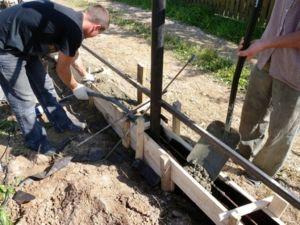 Процесс заливки фундаментной основы ограждения бетонной смесью