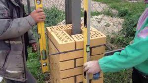 Способ кладки кирпичного опорного элемента ограждения с использованием прутков