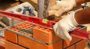 Процесс кладки кирпича опор ограждения сопровождается измерениями